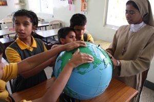 wychowankowie szkoły w Nongbah z siostrą oglądają globus